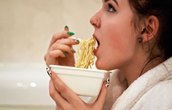 A woman prepares to eat some noodles