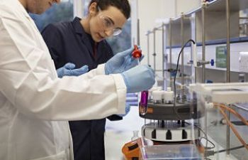 Two scientists, one in the foreground wearing a white lab coat and a second behind wearing a navy blue lab coat, looking at a purple liquid in a test tube