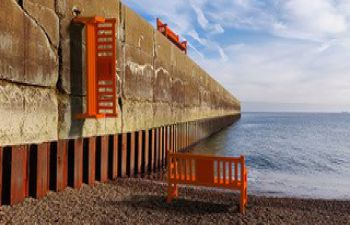 An orange bench on the beach facing the sea with a similar bench vertically attached to a wall
