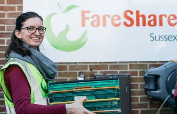 University of Sussex student Anna Maukner, wearing a high vis jacket, is carrying plastic containers in front of the FareShare logo
