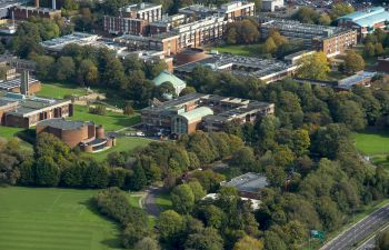 A view from above of the University of Sussex campus surrounded by green fields and trees