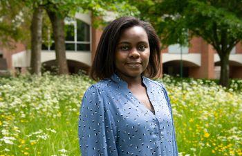 Tamanda Maggie Gomani, Mandela Scholar, in front of grass and a red brick Sussex campus building