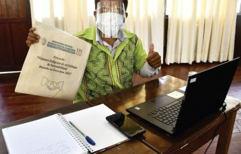 A student sitting in front of a laptop wearing PPE holding up a branded UNIA bag and giving a thumbs up