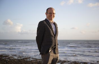 Photo of Prof Benjamin Sovacool standing on a beach with the sea behind him