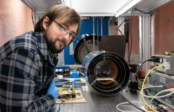 Thomas Coussens in the quantum lab looks at the camera