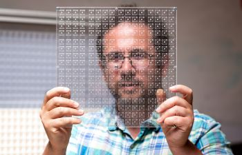 Dr Gianluca Memoli is dressed in a brightly coloured check shirt and is holding a piece of transparent material across his face