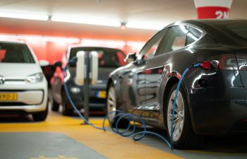 Black, white and grey electric cars are parked and being charged in a multi-storey car park