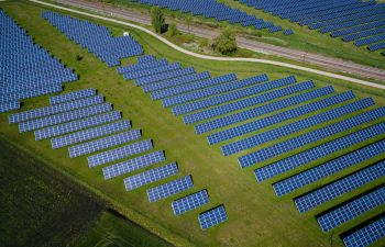 Rows and rows of blue solar panels on a green hill