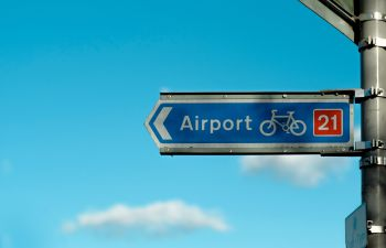 A blue sign pointing the route of a cycle lane to an airport
