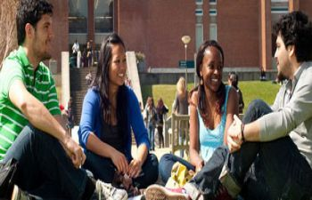 Four students sit cross legged facing each other with the University of Sussex library in the back