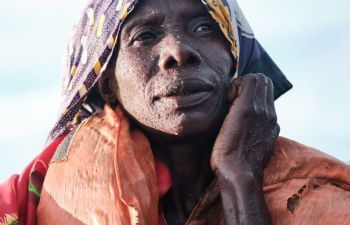 Maama Nankya, the woman in the photograph, looks out to the horizon with raindrops on her face, after a passing thunderstorm.
