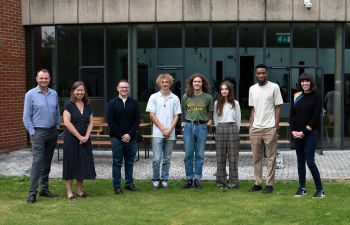 Members of the Pitch for the Planet judging panel and winning entrants stand in a line with the university campus as a backdrop