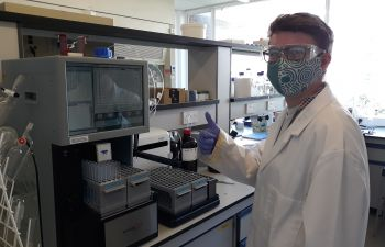 Charlie in the Chemistry lab with a face covering, giving a thumbs up