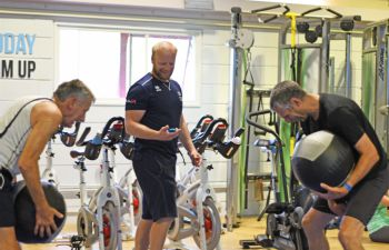 A Sussexsport instructor leads a circuits class while two men workout at the Sport Centre