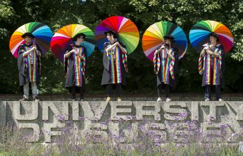 Five students stand atop the concrete University of Sussex sign wearing special rainbow gowns and holding rainbow umbrellas