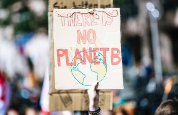 A hand holds up a protest sign reading 'No Planet B' in red hand-drawn lettering, with a drawing of the earth on fire underneath.