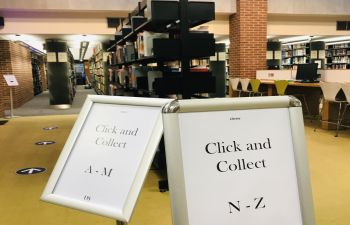 Two poster stands which read respectively 'Click and Collect A-M' and 'Click and Collect N-Z', placed in front of the Click and Collect shelving units.