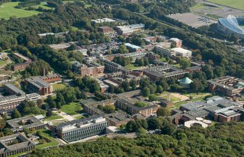 An aerial view of the University of Sussex campus showing the buildings among the green of trees