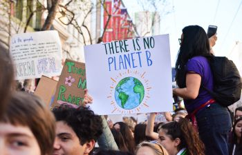 A large group of climate protesters hold up signs