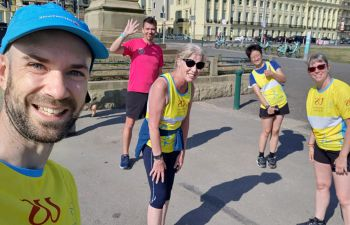 Five Team Sussex runners on Brighton seafront, wearing yellow vests or t-shirts