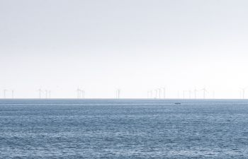 Long distance shot of a row of wind turbines out at sea