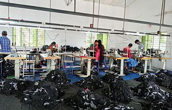 A room of a textiles factory with people working and clothes on the floor