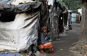 A woman of colour sitting on the floor with her back against tents made with scraps