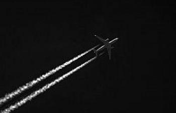 Airplane crossing a black sky