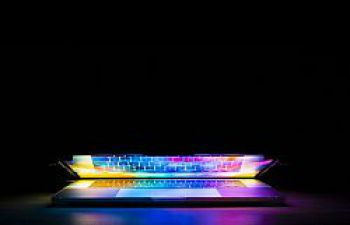 Semi-open laptop in a dark room, reflecting colourful light