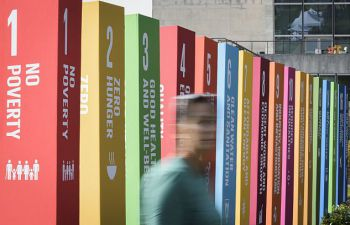 Woman passing by in front of banners representing each of the sustainable development goals