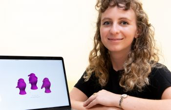 Claire Lancaster is wearing a black top and sits beside a computer screen displaying three purple images on a white background