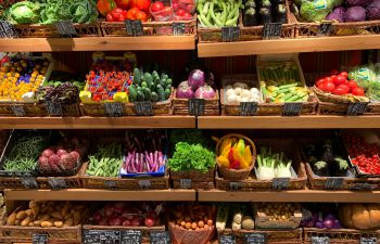 A wide variety of fruit and vegetables stacked on supermarket shelves