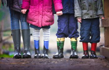 Four children stand facing the camera with muddy wellington boots. The image only pictures the children from the torso down.