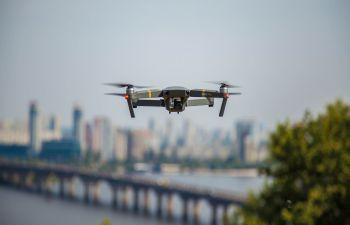 A small drone hovers in the air with a cityscape in the background including a bridge over a wide river