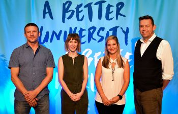 From left to right: Mika Peck, Lucy Hughes,  Melissa Lazenby and Pete Newell stand in front of a light blue backdrop which reads 'A Better University for a Better World'