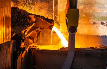 Hot molten metal is poured into a large container at a steel factory