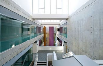 a photograph inside Jubile building, looking down from the top landing onto stairways and glass panels