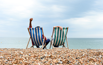 Two people sitting on deckchairs on Brighton beach