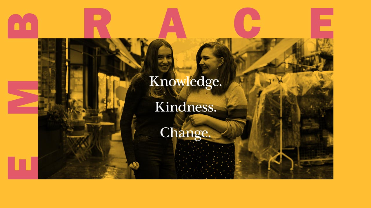 Friends Olivia and Jessica, behind the text 'Embrace knowledge; Embrace kindness; Embrace change'