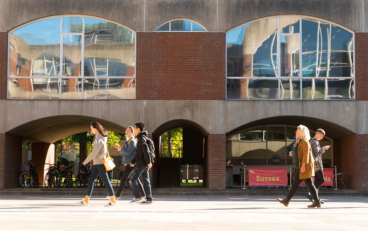students walk by falmer house on campus