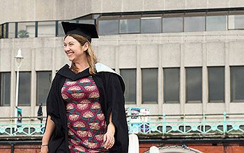 graduate standing in front of the Brighton Centre