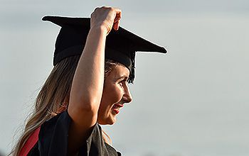 A student in a gown puts her mortar board hat on her head