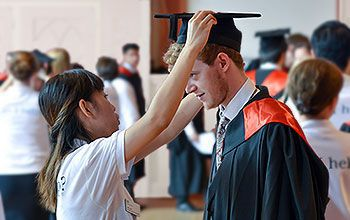 A student gets gowned in the robing room