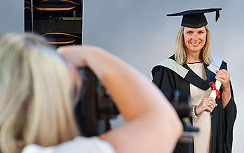 A student gets her picture taken professionally at her graduation ceremony