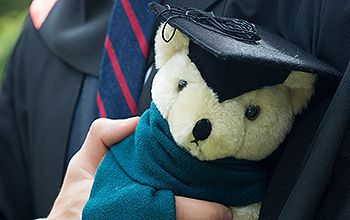 A graduate holding a teddy bear bought from the souvenir stall