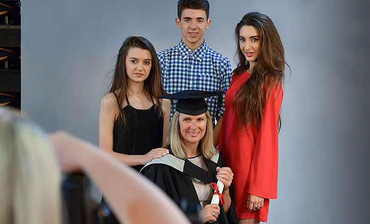 A graduand gets photographed with her family at a ceremony