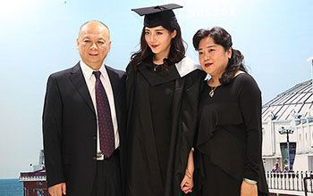 A graduate with her family at an overseas celebration