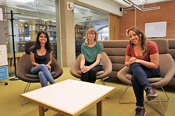 Three PhD students sit in chairs in front of a white table in Sussex Research Hive