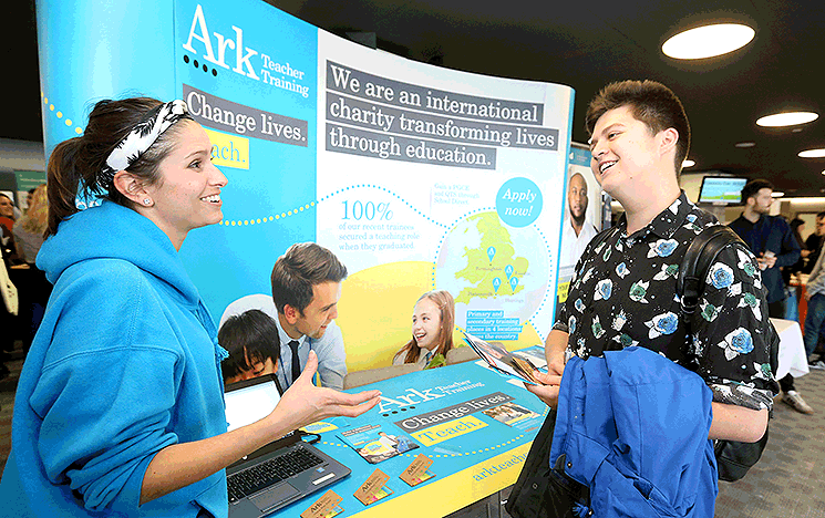 A student talking to a potential employer at a University of Sussex careers fair