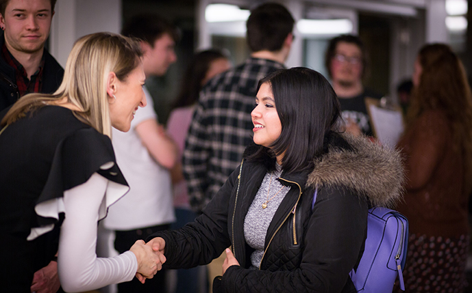 An employer shaking hands with a business student at Sussex's Graduate Careers' Fair